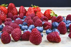 Gesunde Mischfrucht und Bestandteile mit Erdbeere, Himbeere, Blaubeere Beeren auf rustikalem weißem hölzernem Hintergrund Lizenzfreies Stockbild