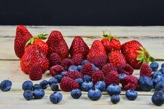 Gesunde Mischfrucht und Bestandteile mit Erdbeere, Himbeere, Blaubeere Beeren auf rustikalem weißem hölzernem Hintergrund Stockfoto
