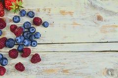 Gesunde Mischfrucht und Bestandteile mit Erdbeere, Himbeere, Blaubeere von der Draufsicht Beeren auf rustikalem weißem hölzernem Lizenzfreie Stockfotografie