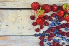 Gesunde Mischfrucht und Bestandteile mit Erdbeere, Himbeere, Blaubeere von der Draufsicht Beeren auf rustikalem weißem hölzernem Stockfoto