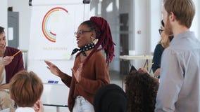 Gesunde multiethnische Arbeitsplatzdiskussion, junger afrikanischer weiblicher Chef, der mit verschiedenen Bürokollegen gedanklic stock footage