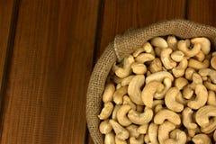 Gesunde Nahrung Acajounuss in der Sacktasche auf hölzernem Tabellenhintergrund Lizenzfreie Stockbilder