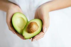Gesunde Nahrung Avocado in den Frauen-Händen stockfotos