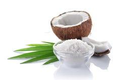Gesunde Nahrung Frische Kokosnuss mit Flocken in der Glasplatte und in den grünen Palmblättern stockfotografie