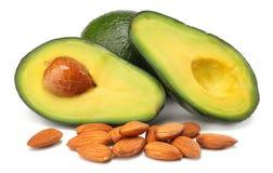 Gesunde Nahrung geschnittene Avocado mit den Mandeln lokalisiert auf weißem Hintergrund Lizenzfreie Stockfotos