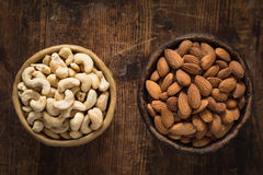 Gesunde Nahrungsmittel: Schüssel Acajoubäume und Mandeln auf Holztisch Stockfotos