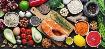 Gesunde Nahrungsmittelsaubere Essenauswahl: Fische, Frucht, Nüsse, Gemüse, Samen, superfood, Getreide, Blattgemüse auf schwarzem  stockfoto