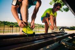 Gesunde Paare, die ihre Spitzee von Laufschuhen auf Bank binden lizenzfreie stockfotografie
