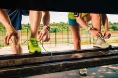 Gesunde Paare, die ihre Spitzee von Laufschuhen auf Bank binden stockbilder