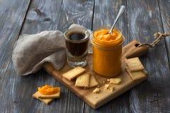 Gesunde rohe Orangenmarmelade mit getrockneten Aprikosen in einem Glasgefäß mit Plätzchen Lizenzfreies Stockfoto
