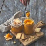 Gesunde rohe Orangenmarmelade mit getrockneten Aprikosen in einem Glasgefäß mit Plätzchen Stockfoto