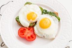 Gesunde Sandwiche mit Spiegeleiern und Tomate des Spinats auf einer weißen Platte Lizenzfreies Stockfoto