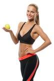 Gesunde schöne Blondine, die einen Apfel halten Stockfoto