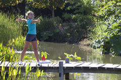 Gesunde schöne junge Frau, die auf Brücke und Wasser ausarbeitet Stockfoto