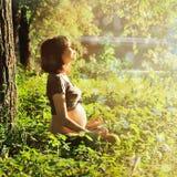 Gesunde schwangere Frau, die Yoga im Park tut. Stockfoto
