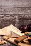 Gesunde snaks von der unterschiedlichen Art des Käses, der Nüsse und der Pflaumen Lizenzfreie Stockbilder