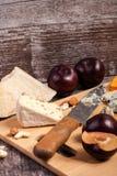 Gesunde snaks von der unterschiedlichen Art des Käses, der Nüsse und der Pflaumen Stockfotografie