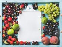 Gesunde Sommerobstsorte Feigen-, Schwarze und Grünetrauben, süße Kirschen, Erdbeeren, Pfirsiche auf Blau malten hölzern Stockfoto