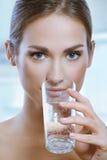 Gesunde Sportfrau, die kaltes Wasser vom Glas trinkt Stockfotos