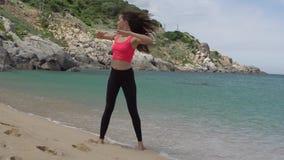 Gesunde sportliche Frau, die für das Aufwärmen bevor dem Laufen auf Strand nahe Meer trainiert Frau, die Drehenkörperübung tut stock footage