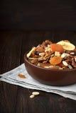 Gesunde Trockenfrüchte und Nüsse in der Schüssel auf hölzernem Hintergrund Stockbild
