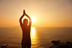 Gesunde Yogafrauenmeditation an der Sonnenaufgangküste Lizenzfreie Stockfotos