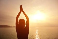 Gesunde Yogafrauenmeditation an der Sonnenaufgangküste Lizenzfreies Stockfoto