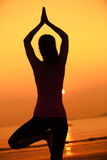Gesunde Yogafrauenmeditation an der Sonnenaufgangküste Lizenzfreie Stockbilder