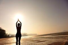 Gesunde Yogafrauenmeditation an der Sonnenaufgangküste Stockfoto