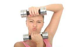 Gesunder aggressiver entschlossener Sitz-junge Frau, die stumme Bell-Gewichte hält Stockfoto