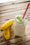 Gesunder Banane Smoothie auf weißem hölzernem Hintergrund stockbilder