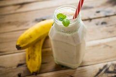 Gesunder Banane Smoothie auf weißem hölzernem Hintergrund stockfotografie