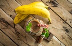 Gesunder Banane und Schokolade Smoothie auf weißem hölzernem Hintergrund lizenzfreie stockfotografie