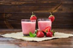 Gesunder Erdbeerjoghurt mit tadellosen Blättern und frischen Beeren an Stockbild