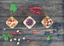 Gesunder Frühstück Jogurt und Corn Flakes mit Beeren in den Gläsern auf rustikalem hölzernem Hintergrund Geschenke der gesunden E lizenzfreie stockfotos