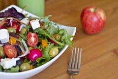 Gesunder grüner Salat und ein Apfel auf Holztisch Stockfotos