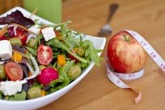 Gesunder grüner Salat und ein Apfel mit messendem Band Lizenzfreies Stockbild