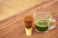 Gesunder grüner Tee in der Schale und Bambus wischen Stockfotografie