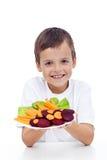 Gesunder Junge mit Frischgemüse auf Platte Lizenzfreies Stockfoto