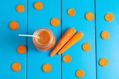 Gesunder Karotte Smoothie in einem Glas auf blauem hölzernem Hintergrund Stockbild