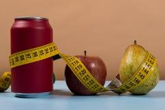 gesunder Lebenkontrast mit Dose Soda und Frucht mit einem Maßband lizenzfreie stockfotos