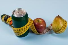gesunder Lebenkontrast mit Dose Soda und Frucht mit einem Maßband lizenzfreies stockbild