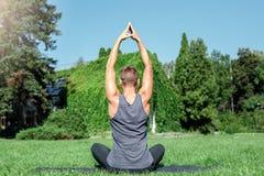Gesunder Lebensstil Übendes Yogafreien des Mannes, welches oben die hinteren meditierenden Hände ruhig sitzt lizenzfreies stockfoto