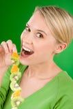 Gesunder Lebensstil - Frauenkiwi und -orange auf Steuerknüppel lizenzfreie stockbilder