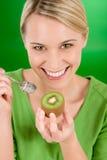 Gesunder Lebensstil - glückliche Frauenholdingkiwi Stockfotos