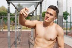 Gesunder Lebensstil Hemdlose Stellung des jungen Mannes, die draußen selfie auf dem Smartphone schaut die Kamera überzeugt nimmt lizenzfreies stockbild