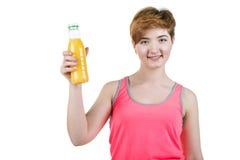Gesunder Lebensstil, richtige Nahrung Ein junges Mädchen mit einer Flasche Orangensaft im Huhn, lächelnd, auf einem Weiß lokalisi Lizenzfreies Stockfoto