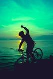 Gesunder Lebensstil Schattenbild des Radfahrers das Fahrrad an Se reiten Lizenzfreies Stockbild