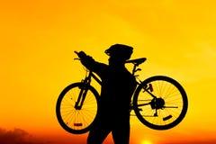 Gesunder Lebensstil Schattenbild des Radfahrers sein Fahrrad tragend Stockbild