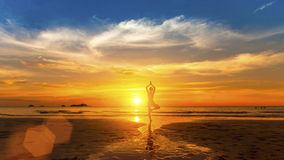 Gesunder Lebensstil Silhouettieren Sie Meditationsyogafrau auf Hintergrund des Meeres und des Sonnenuntergangs Stockbilder